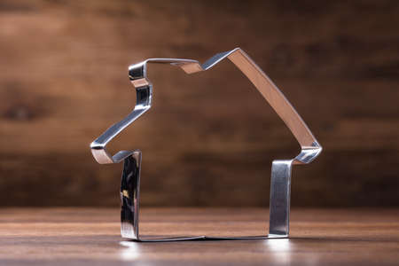 Still Life Of Stainless Steel House Cutter On The Wooden Desk Stock Photo