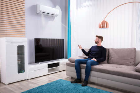 Young Man Sitting On Sofa Using Air Conditioner At Home