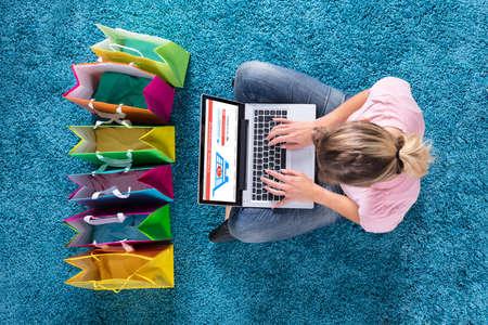 Vista elevada de uma mulher sentada no tapete e compras on-line com sacolas de compras Foto de archivo