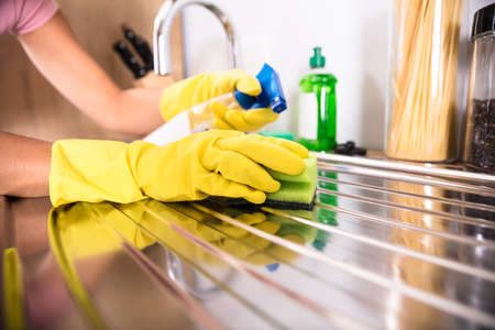 Close-up Of Persons Hand Wearing Yellow Gloves Cleaning Stainless Steel Sink With Sponge Stock Photo