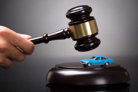 Close-up Of A Judges Hand Striking Gavel On Small Car In Courtroom Reklamní fotografie