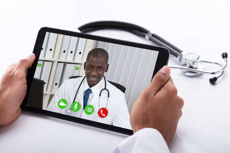 Close-up Of A Doctor's Hand Video Conferencing With African Male Colleague On Digital Tablet Banque d'images