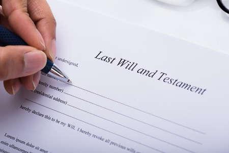 Nahaufnahme der Hand einer Person, die letzten Willen und das Testament ausfüllt, bilden sich