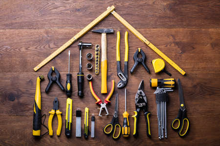 Elevated View Of Many Tools With Roof Made With Yellow Measuring Tape On Wooden Table Фото со стока