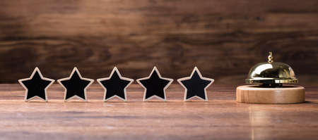 Black Five Stars Shape Arranged In Row With Service Bell On Wooden Table Archivio Fotografico