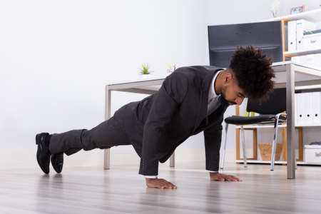 Young Businessman Doing Push Up On Floor At Workplace Stock Photo