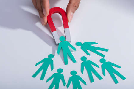 Close-up Of A Businesspersons Hand Holding Red Horseshoe Magnet Attracting Paper Candidates On Desk Stock Photo