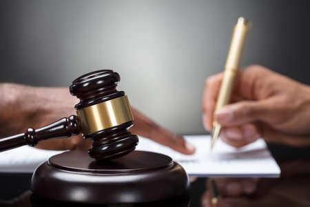 Close-up Of A Gavel Ręką Osoby Podpisanie Dokumentu Prawnego Na Drewniane Biurko