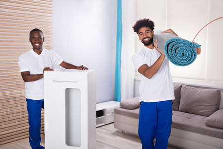 Portrait Of Two Male Movers With Cabinet And Rolled Up Carpet In The Living Room Foto de archivo