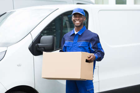 Delivery Man Standing Near The Van Holding Cardboard Box