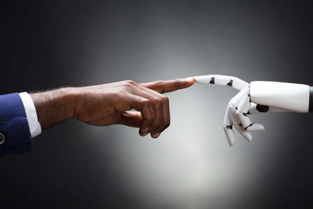 Fingers Of Robot And Man Touching Against Gray Background