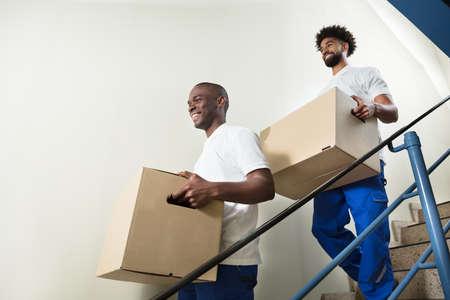 Portrait de deux jeunes migrants souriants debout sur un escalier tenant des boîtes en carton