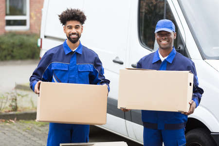 Close-up Of Two Delivery Men Holding The Cardboard Boxes