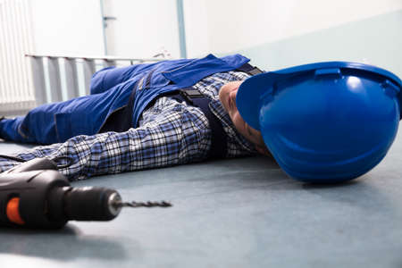 Close-up Of Handyman's Helmet With Unconscious Handyman Lying On Floor