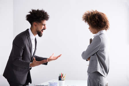 Angry Young Businessman Shouting At Female Executive In Office