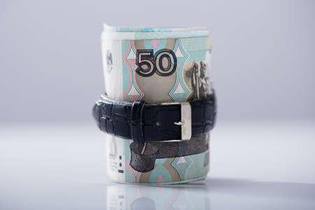 Oben gerollt russische Rubel gebunden mit Gurt gegen weißen Hintergrund