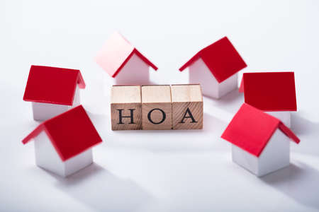Homeowner Association Wooden Blocks Surrounded With Miniature House Models Over The White Background 스톡 콘텐츠