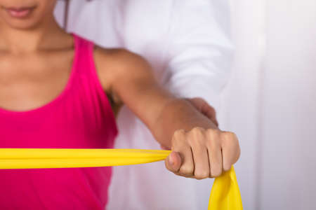Physiotherapist Assisting Woman While Exercising With Exercise Band