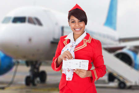 Portrait Of A Smiling Young Stewardess In Front Of Airplane Stock Photo