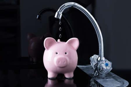 Kropelki wody kapią w różowej skarbonce z kranu zlewozmywaka kuchennego