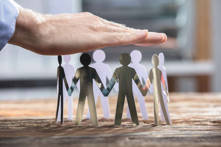 Close-up Of A Businesspersons Hand Protecting Human Cut-out Figures On Wooden Desk Stock Photo