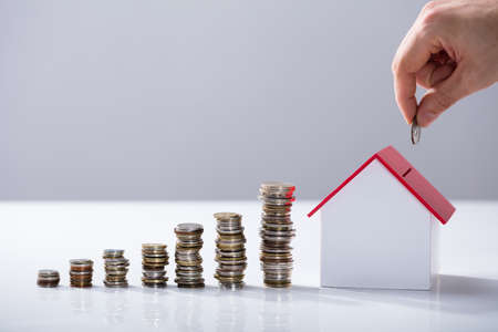 Person's Hand Inserting Coin In The House Model With Increasing Coins Stack On Desk
