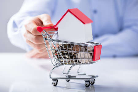 Mans Hand Holding Shopping Cart Filled With Coins And House Model On The White Desk Stok Fotoğraf