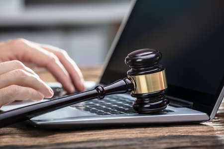 Close-up Of A Businessperson's Hand Using Laptop With Gavel On Wooden Desk