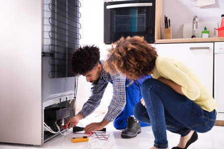 Woman Looking At Technician Examining Refrigerator With Digital Multimeter In Kitchen 스톡 콘텐츠