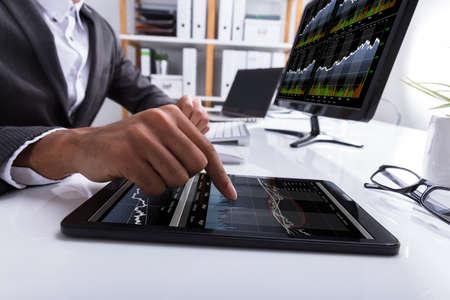 Gros plan de la main d'un homme d'affaires travaillant avec graphique sur tablette numérique au lieu de travail Banque d'images