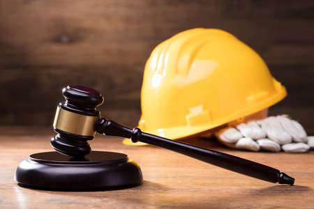 Judge Gavel In Front Of Yellow Safety Helmet On The Wooden Table