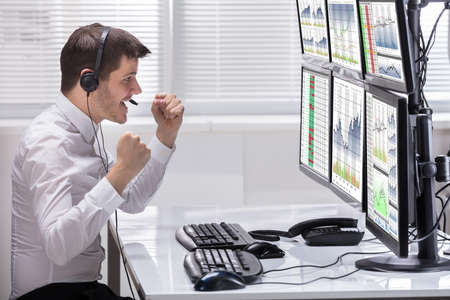 Side View Of A Happy Male Stock Market Broker Looking At Rising Stock Charts