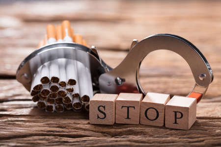 Close-up Of Cigarettes And Handcuff With Wooden Blocks Showing Stop Word On Desk