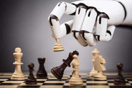 Close-up Of A Robots Hand Playing Chess