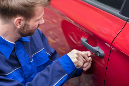 Close-up Of A Human Hand Opening Red Car's Door With Lockpicker