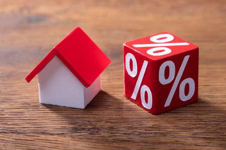Nahaufnahme des Haus-Modells And Percentage Red Block auf dem Holztisch Standard-Bild