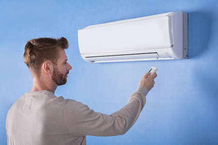 Rear View Of A Young Man Operating Air Conditioner Mounted On Blue Wall Stock Photo