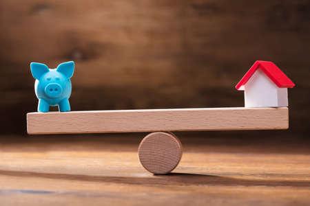 木製シーソー上のブルーピギーバンクとミニチュアハウスモデルのバランス