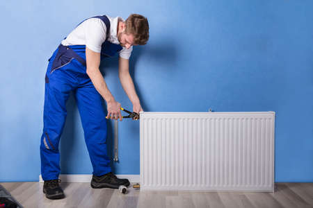 Young Male Plumber In Uniform Installing Radiator With Wrench Stock Photo