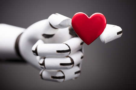 Close-up Of A Robots Hand Holding Red Heart Stock Photo
