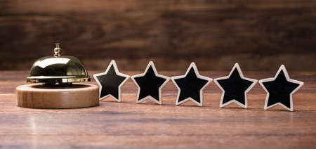 Black Five Stars Shape Arranged In Row With Service Bell On Wooden Table Stock Photo