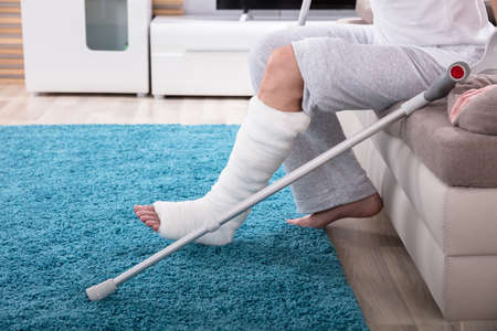 Young Man With Broken Leg Using Crutches To Get Up From Sofa