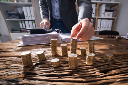 Businessperson Calculating Stacked Golden Coins With Calculator On Wooden Desk Фото со стока