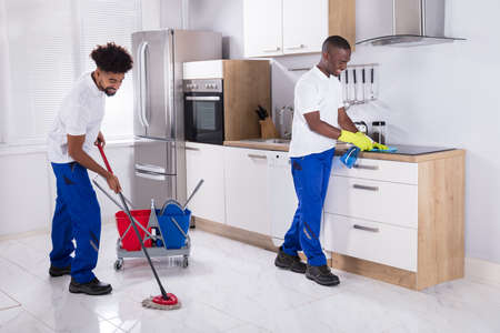 Two Smiling Male Janitor Cleaning The Induction Stove And Mopping Floor In The Kitchen Stock Photo
