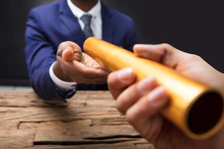 Close-up Of A Businessmans Hand Passing Golden Relay Baton To His Partner