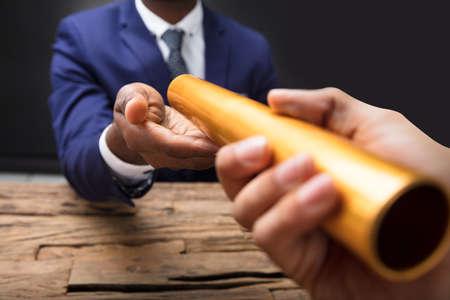 Close-up van de Hand die van een Zakenman Gouden Relaisknuppel doorgeven aan Zijn Partner