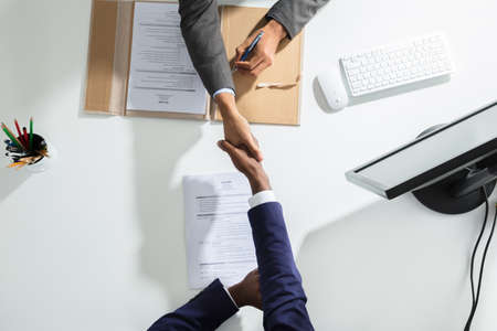High Angle View Of Businessperson Shaking Hand With Candidate Over White Desk Stockfoto