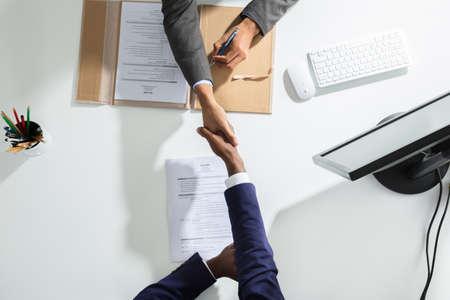 vista de ángulo alto de hombre de negocios que sacuden la mano con el candidato sobre escritorio blanco Foto de archivo