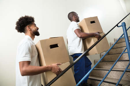 Two Young Male Worker Holding Cardboard Boxes While Climbing Steps At Home