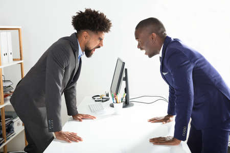 Two Angry Young Businessmen Shouting At Each Other At Workplace Foto de archivo